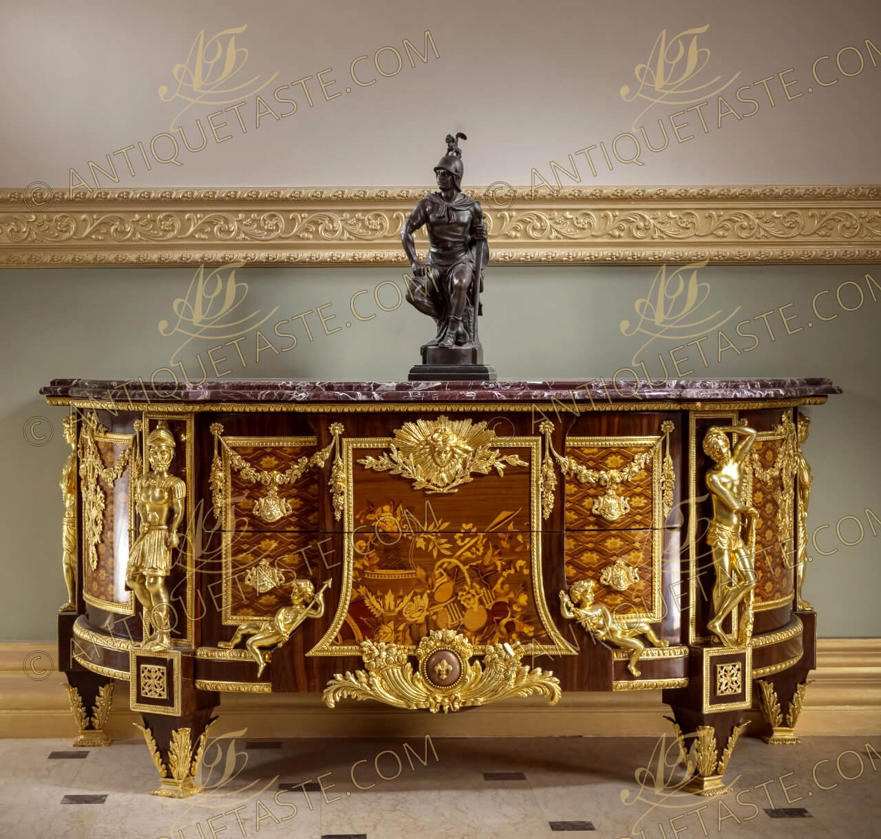 A French ormolu-mounted marquetry and parquetry D shaped commode, after the model by Jean-Henri Riesener, Circa 1890, surmounted by a shaped and stepped veined marble top, centered to the front by a pair of drawers headed by an sunburst winged mask ormolu mount, with central panel inlaid sans traverse with an ewer and basket of fruit and flowers flanked on each side by cherubs emblematic of Bienfaisance and Justice, above a fleur-de-lys-studded ormolu globe and cornucopia, flanked to each side by inlaid parquetry cupboard door hung with floral swags and ribbon-suspended military trophies, the angles mounted with imitation of the four armorial emblematic of Courage, Force, Prudence and Tempérence, on tapering acanthus-mounted feet