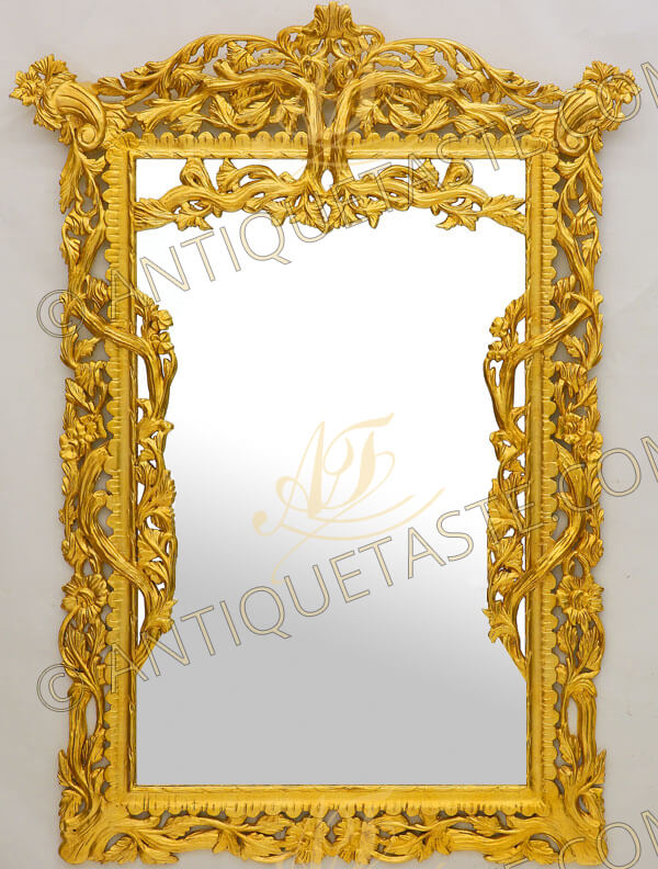 A charming Italian early 19th century style rectangular shaped giltwood wall mirror, hand carved and gilded with 18th carat French gold foils, The mirror plate is surrounded by a heavily and richly carved pierced frame in lavish design of leafy works, sunflowers and entwined tree branches. With two cornucopias on each top corner symbol of abundance and nourishment, The internal Cyma Recta motif internal frame with  twisted internal border issuing scrolled foliage branches to sides and to the top central reverse
