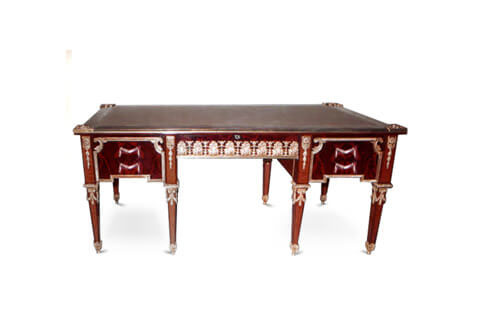 An Opulent Continental 18th century Louis XVI style crouch mahogany and ormolu-mounted executive desk, The desk is raised on eight square tapered legs each with ormolu top detailed festoon pendants headed with a hammered wrap around ormolu trim and terminating with wrap around ormolu acorn finial sabots. The long vertical block above each long adorned with fine square rosette issuing imbricated laurel pendants, At each side are four drawers, 'sans traverse', displaying the warm and fine crouch mahogany grain continuing from one drawer to the other, Each set of two framed within a fine chiseled ormolu border with C scrolls connections and swaging drapes shaped handle to each one, At the recessed apron is a central drawer decorated with a sensational and high quality satin and burnished finished pierced acanthus leaves chain band ormolu mount above a beveled ormolu trim and an ormolu keyhole escutcheon, At each side panel are fine repeat mahogany panels displaying the warm grain and framed within the same ormolu band and C scrolls connections, Above, framed in an ormolu gallery is the gilt tooled fitted leather writing surface with four foliate ormolu clasps to each corner. Three sectional leather top surface in another version. The back is identically decorated with no drawers, The desk is available in a set includes three tables of an identical design of the desk with a marble top