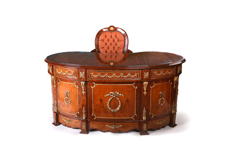 A graceful French Neoclassical style mahogany and veneer inlaid ormolu-mounted kidney shaped executive desk, The veneer inlaid filet sectional moulded kidney shaped top above three drawers ornamented with ormolu festoons, ormolu trims and lyre shaped handles, separated by blocks ornamented with ormolu rosettes, above two deep drawers to each side framed with ormolu trim connected with foliate C scrolls and scrolled ormolu handles, The four side supports flanking the drawers ornate with ormolu Ancone of Bracket, all above a scalloped shaped plinth with blocks and faux drawers decorated with Neoclassical style ormolu mounts, The back side has the same design all over, the central three sections ornamented with ormolu knotted ribbons and circular laurel wreath and ribbon tied laurel hanging tassels