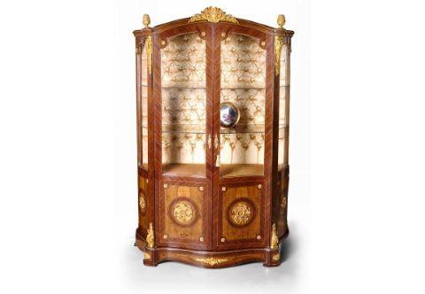 A French Napoleon style ormolu-mounted veneer inlaid China Cabinet, The domed eared top crested with central ormolu mount and ormolu pine cones above two full size quarter sans traverse veneer inlaid doors, with glazed panels, ormolu rosettes, and ormolu keyhole escutcheons, With two glass shelves on a velvet upholstered tufted background, The lower part of the doors adorned with finely chiseled large flower rosettes ormolu mounts placed on waterfall bubinga veneer background within a circular palisander filet and opens to reveal one shelf inside, The corner supports ornamented with richly cast acanthus ormolu volute chutes on top and bottom above the ormolu mounted serpentine shaped plinth, The sides with glazed panels and similarly designed as the front, Luxurious vitrine, corner furniture, Serre Bijoux, Francois Linke-vitrine, jean-henri riesner vitrine, Leon Message vitrine, Francois Linke display cabinet, cabinet vitrine, Louis xv vitrine, Louis xvi vitrine, ormolu mounted vitrine, Louis XIV vitrine, display cabinet, vernis martin style vitrine, French style vitrine, glass vitrine, English style vitrine, veneer inlaid vitrine, marquetry vitrine, Italian style vitrine, glass round vitrine, boulle style vitrine, antique reproduction vitrine, antique style display cabinet, empire style bookcase vitrine, display cabinet with porcelain plaque, French style Vitrine, English Style Vitrine, Ormolu-mounted Vitrine, Louis XV style Vitrine, Vernis Martin style painted Vitrine, Antique style Vitrine, Antique style Glass Cabinet, Antique style Corner Vitrine, Andres Charles Boulle Vitrine, Carved Vitrine, Antique Display Bookcase, High Quality Antique Furniture Reproductions, Antique Furniture, antique furniture manufacturer in egypt, antique furniture gallery, antique furniture store