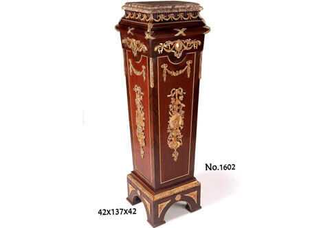 French Empire style ormolu-mounted veneer inlaid vase stand / pedestal, marble topped, and ornamented with gilt ormolu mounts of scrolling hanging foliage medallions, ribbons, trophies and musical instruments, the central part is inlaid with Bubinga veneer surrounded with ormolu beaded encadrement and veneered outside with palisander veneer, raised on a shaped rectangular base ornamented with ormolu beaded encadrement frieze and gilt-ormolu rosettes