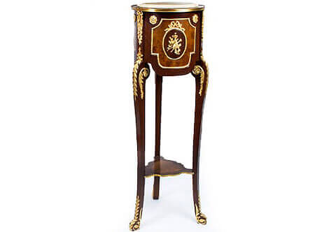 Régence style Pedestal, French Régence style Stand, Luxurious Pedestals, Jean-Henri Riesner Pedestal, Francois Linke Pedestal, Maison Millet Pedestal, Corners Decoration, French style Stand, Andres Charles Boulle Pedestal, Theodore Millet Style Pedestal, Robert Adam style Vase Stand, Empire Style Pedestal, Vitrine Stands, Louis XV style Pedestals, Bombe Shape Stand, Louis XVI Pedestals, Ormolu-mounted Stand, English style Pedestal, Empire style Pedestal, George III style Pedestals, Heritage Pedestals, Display Stands, French Régence style mahogany ormolu-mounted veneer inlaid torcheres pedestal, The inset beveled and moulded marble top within a brass bad above a double veneer inlaid three sectional circular cylinder body, each section is centered with ormolu musical instruments medallion mount within ormolu ribbon tied oval beaded frame bordered with another shaped beaded encadrement flanked to each upper concave side with an ormolu flower rosette, Each block between sections is ormolu adorned with a fine ribbon tied suspending foliage confronting a richly chiseled large ormolu laurel chutes applied to each leg, The body is resting a tall cabriole slender S scrolled supports headed with a flower rosette issuing a scrolling acanthus leaf terminating with laurel leaves on the front part of the turning leg and a musical trumpet with rosette issuing acanthus leaf to each side. The supports are connected with a veneer inlaid shaped bottom tier ornamented with a hammered brass band