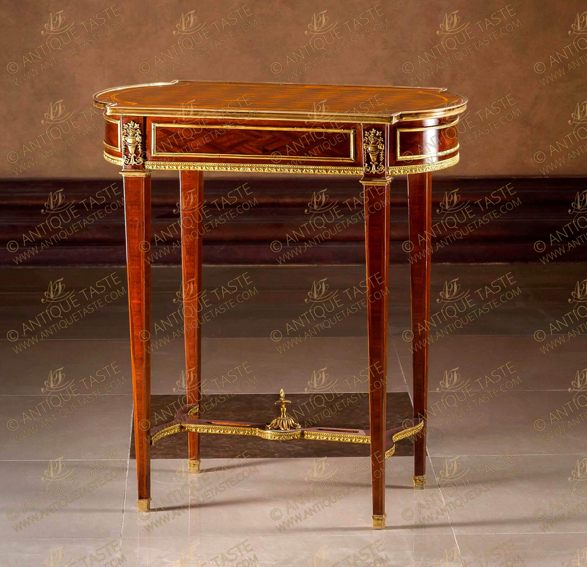 A dignified French mid 19th century Louis XVI Neo-classical style gilt-ormolu-mounted and parquetry inlaid Table À Ouvrage after the mode by Maison Kriéger, The oval breakfront top has a crossbanded veneer and parquetry inlays within a molded gilt-ormolu gallery above a conforming sectional frieze with one drawer and borders of ormolu filets, separated by block ornamented by Neo-classical style gilt-ormolu mounts of beaded and reeded vase issuing floral Rinceaux style and bouquet of blossoming foliate branches. The apron is bordered to the bottom with exquisitely chased ormolu designed gallery, Raised by slender tapered legs with ormolu trim finished with ormolu sabots and top ormolu crown, The legs are joined by a pierced waved sides stretcher elegantly decorated by a beaded and foliate ormolu trim with a central ormolu foliate movements final